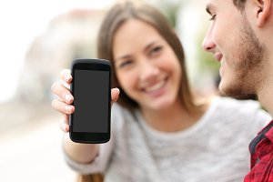 Couple showing apps in a blank smart phone screen.jpg
