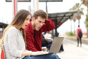 Couple surprised watching a laptop in a train station.jpg