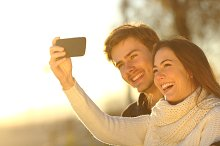 Couple taking selfie photo with a smart phone at sunset.jpg