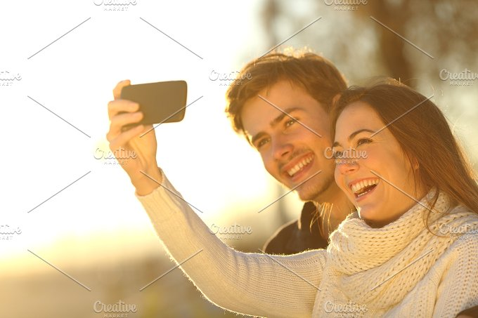 Couple taking selfie photo with a smart phone at sunset.jpg - Technology
