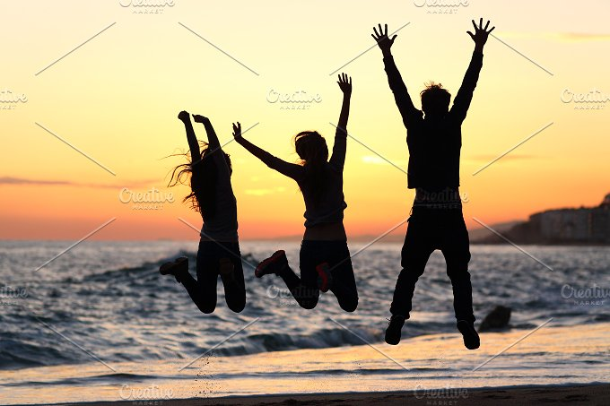 Friends silhouette jumping happy on the beach at sunset.jpg - People