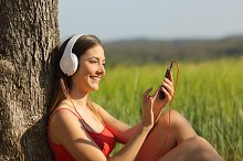 Girl listening to the music and downloading songs in a field.jpg