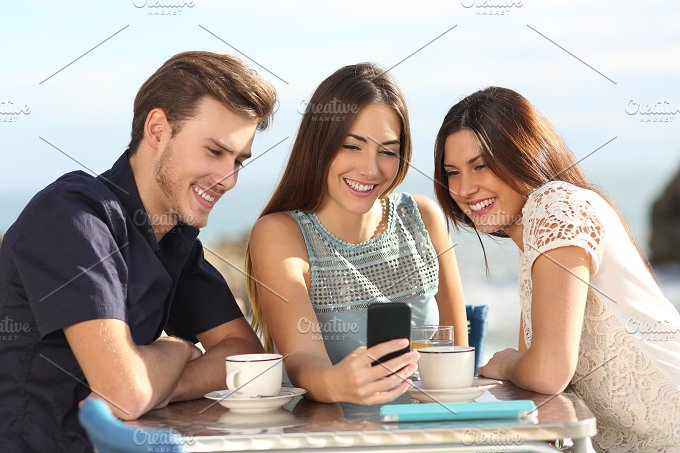 Group of friends watching social media in a smart phone.jpg - Technology
