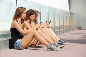 Group of three teenager girls typing on the mobile phone.jpg