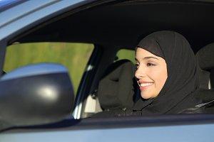 Happy arab saudi woman driving a car.jpg