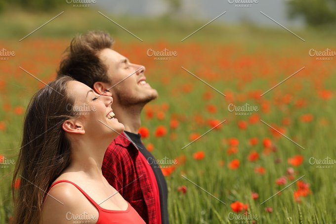 Happy couple breathing fresh air in a red field.jpg - People