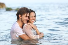 Happy couple in love hugging and bathing in the beach.jpg