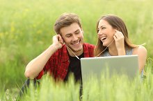 Happy couple or friends sharing music from a laptop.jpg