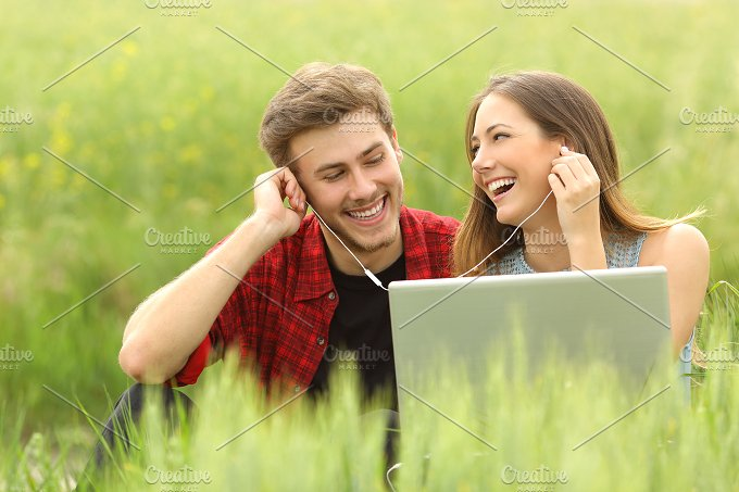 Happy couple or friends sharing music from a laptop.jpg - Technology