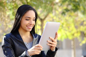 Happy woman reading a tablet reader in a park.jpg