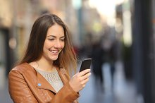 Happy woman using a smart phone in the street.jpg