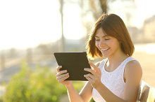 Happy woman using a tablet outdoors.jpg