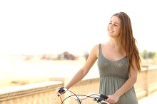 Healthy teen girl walking with a bike in summer.jpg