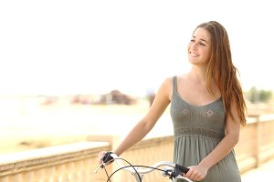 Healthy teen girl walking with a bike in summer.jpg