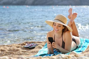 Pretty happy woman reading a smart phone on the beach.jpg