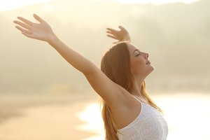 Relaxed woman breathing fresh air raising arms at sunrise.jpg