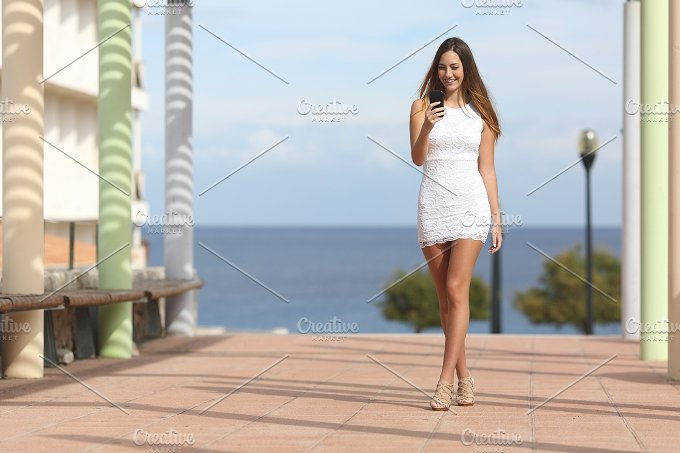 Sexy woman walking and texting on a smart phone.jpg - Beauty & Fashion