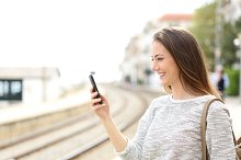 Traveler using a smartphone in a train station.jpg