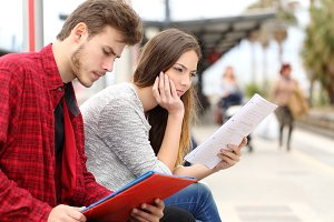 Two students studying waiting transport in a train station.jpg