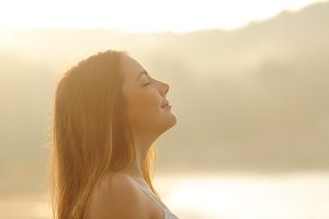 Woman breathing deep fresh air in the morning sunrise.jpg