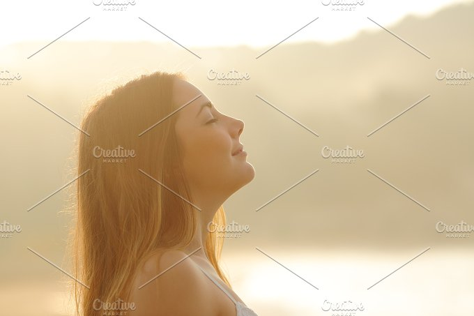 Woman breathing deep fresh air in the morning sunrise.jpg - Health