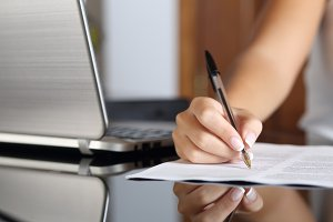 Woman hand writing a contract with a laptop beside.jpg