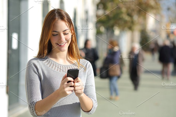 Woman in the street browsing a smart phone.jpg - Technology