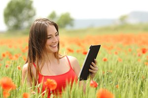 Woman reading ebook in a red field.jpg