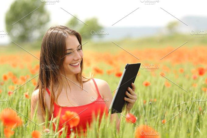 Woman reading ebook in a red field.jpg - Technology