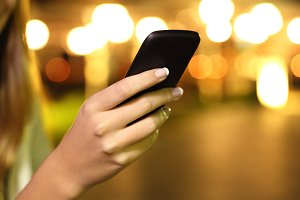 Woman hand using a smart phone in the night.jpg