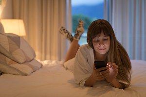 Woman using mobile phone in bedroom