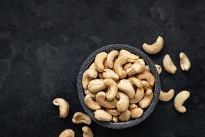 Cashew nuts in bowl on black