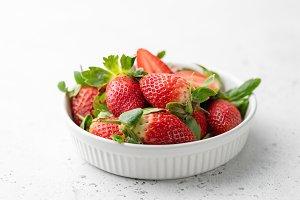 Fresh strawberries in bowl on white