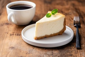 Cheesecake and cup of coffee on wood
