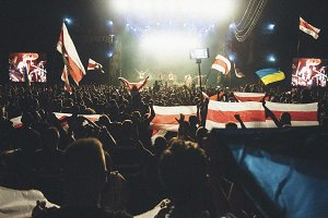 People cheer at a concert with flags