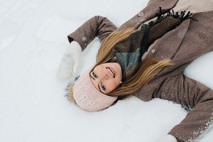 Photo of blonde in hat lying in snow