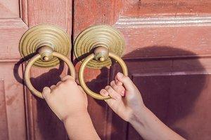 The hand opens the antique door by