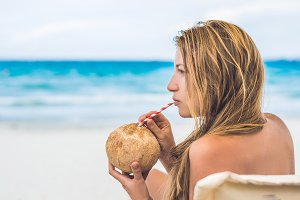 Young woman drinking coconut milk on