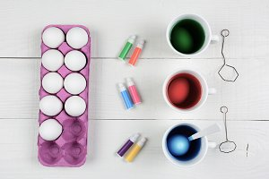 Three cups of dye and eggs with a ca