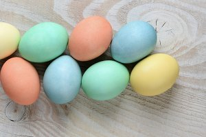Pastel eggs on rustic white table