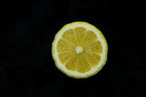half of freshlu lemon on black