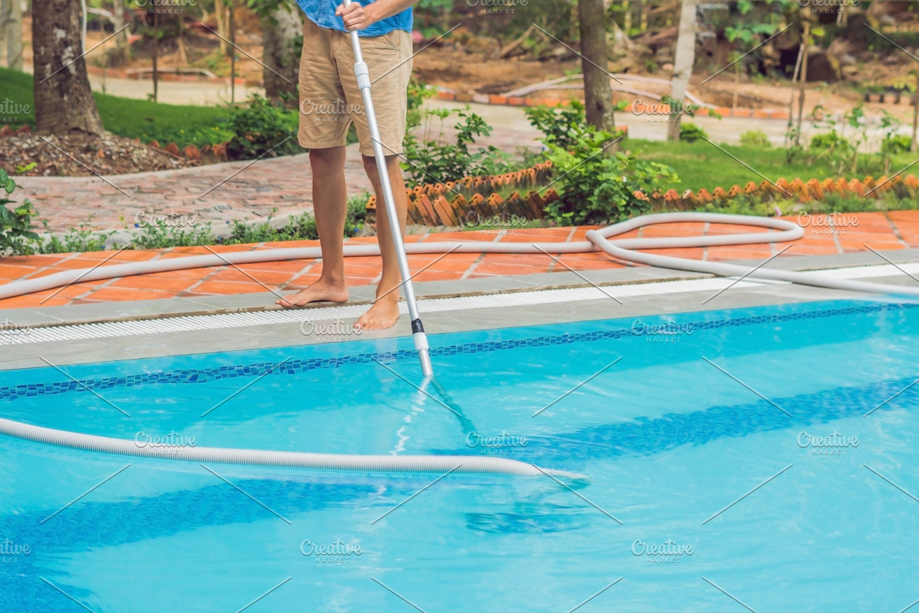 Cleaner of the swimming pool . Man ~ Nature Photos ~ Creative Market