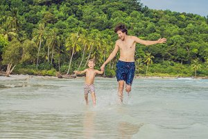 Dad plays with his son in the sea