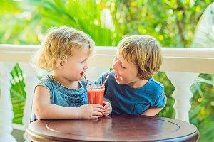 Children boy and girl drink orange