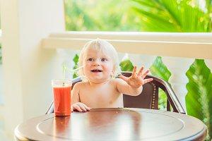 Happy toddler boy drinking healthy