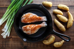 Iron skillet with chicken leggs and