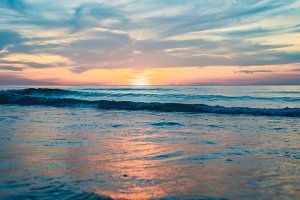 gold sunset over beach with wave