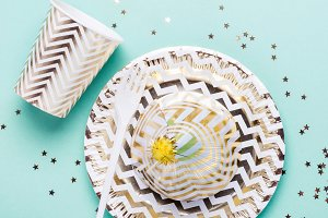 Golden striped dishes on turquoise b