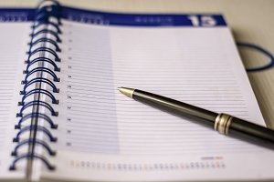 black pen on an open spiral notebook