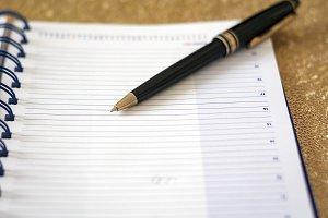 a black pen on an open notebook